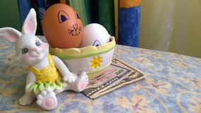 Bunny toy with easter eggs and paper dollars stock photography