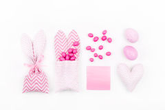 Bunny treat bag with pink candy, empty card, eggs and heart. Easter concept on white background Royalty Free Stock Images