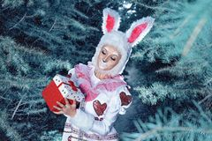 Bunny in a winter forest. A girl wearing a Bunny with a carrot in a winter forest in the handsnn royalty free stock images