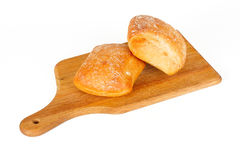 Buns on a breadboard. Two brown buns lying on a breadboard Stock Image