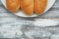 Buns Breads for Breakfast or for Preparing Hot Dogs. Gray Old Wooden Background. White Plate. Copy Space for Text. royalty free stock image