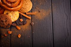 Buns, biscuits, chocolate, nuts, on a wooden table. Around is sprinkled with grated cinnamon. Inside. stock images