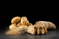 Buns and ciabatta, bread slices on dark wooden table. Barley and fresh mixed breads  on black background Stock Photo