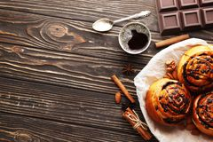 Buns with cinnamon and chocolate on a brown wooden background royalty free stock photos