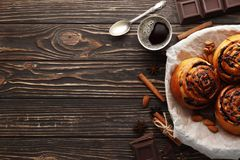 Buns with cinnamon and chocolate on a brown wooden background royalty free stock image