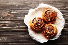 Buns with cinnamon and chocolate on a brown wooden background royalty free stock images