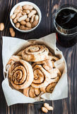 Buns with cinnamon and nuts, cola on a wooden background. Round buns with cinnamon and peanuts on the wooden background Royalty Free Stock Photo