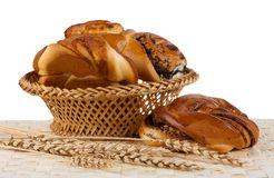 Buns with cinnamon and wheat ears. Isolated. White background Stock Photos