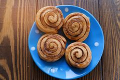 Buns with curl with cinnamon and sugar on a blue polka dot plate wooden background. Breakfast. Homemade fresh pastries. Bakery, stock image