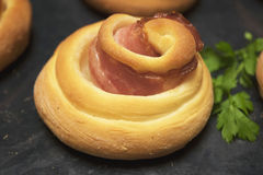 Buns curlicues with bacon. On a black background Stock Images