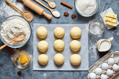 Buns dough traditional homemade preparing recipe, ingridients food flat lay. On kitchen table background. Working with butter, milk, yeast, flour, eggs, sugar royalty free stock image
