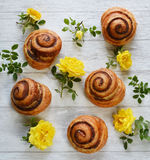 Buns and flowers on the table. Royalty Free Stock Photo