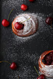 Buns with fresh cherry on dark background Royalty Free Stock Photography