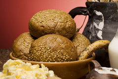 Buns with grains and a black jug. Royalty Free Stock Photography
