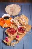 Buns with jam and tea. Some fresh buns with raspberry jam and tea in orange cup stock photo