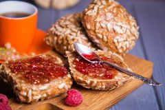 Buns with jam and tea. Some fresh buns with raspberry jam and tea in orange cup stock image