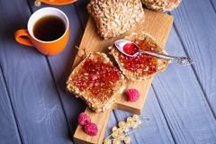 Buns with jam and tea. Some fresh buns with raspberry jam and tea in orange cup stock images