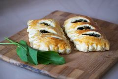 Buns of puff pastry with sorrel close-up. Tasty homemade cakes with greens. Buns of puff pastry with sorrel close-up. Homemade cakes with greens stock image