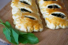 Buns of puff pastry with sorrel close-up. Tasty homemade cakes with greens. Buns of puff pastry with sorrel close-up. Homemade cakes with greens stock images
