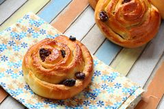 Buns with raisins on colored wooden table Royalty Free Stock Image