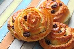 Buns with raisins on colored wooden table Stock Photos
