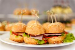 Buns with sesame seeds stuffed with ham and tomatoes stock image