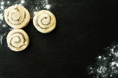 Buns with sugar and poppy seeds,  dough lying on a black stone cutting board sprinkled with flour royalty free stock photography