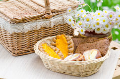 Buns in a wicker basket and a bouquet of flowers Stock Image