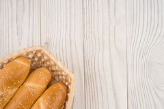 Buns in a wicker basket on old wooden table. Royalty Free Stock Image