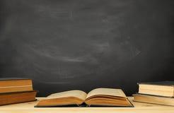 bunt av böcker över träskrivbordet framme av svart tavla arkivbilder