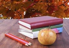 bunt av böcker, blyertspennor och det gula äpplet Serie tillbaka till skolan Arkivfoto