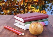 bunt av böcker, blyertspennor och det gula äpplet Serie tillbaka till skolan Royaltyfri Fotografi