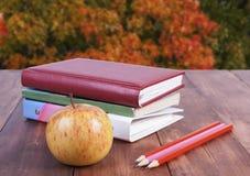 bunt av böcker, blyertspennor och det gula äpplet Serie tillbaka till skolan Arkivbilder