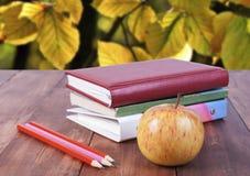bunt av böcker, blyertspennor och det gula äpplet Serie tillbaka till skolan Royaltyfri Foto