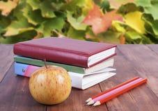 bunt av böcker, blyertspennor och det gula äpplet Serie tillbaka till skolan Fotografering för Bildbyråer