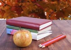 bunt av böcker, blyertspennor och det gula äpplet Serie tillbaka till skolan Royaltyfria Bilder