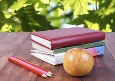 bunt av böcker, blyertspennor och det gula äpplet Serie tillbaka till skolan Royaltyfria Foton