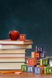 Bunt av böcker med äpplet och träkvarter Arkivbilder