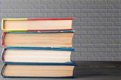 Bunt av böcker med grått murverk i bakgrunden, begrepp av utbildning, vetenskap royaltyfria foton