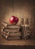 Bunt av böcker och det röda äpplet Royaltyfria Foton
