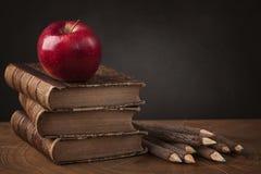 Bunt av böcker och det röda äpplet royaltyfri foto