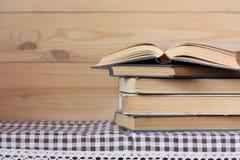Bunt av böcker och en öppen bok på tabellen royaltyfri fotografi