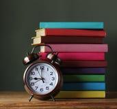 Bunt av böcker och en ringklocka tillbaka skola till Arkivbild