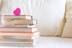 Bunt av böcker och rosa hjärta på den vita sängen Utbildningsbakgrund med kopieringsutrymme, tillbaka till skolabegreppet royaltyfria bilder