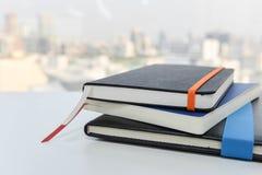 Bunt av böcker på den vita tabellen Fotografering för Bildbyråer