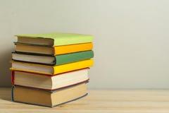 Bunt av böcker på trätabellen sax och blyertspennor på bakgrunden av kraft papper tillbaka skola till Kopiera utrymme för text royaltyfri fotografi