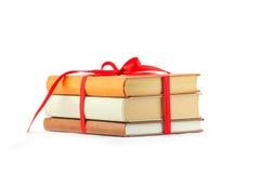 Bunt av böcker som binds upp med det röda bandet som isoleras på en vit backg Arkivfoton