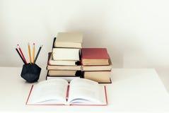 Bunt av bakgrund för bokutbildningsbegrepp, många bokhögar, öppen bok och blyertspennor i konkret hållare på den vita tabellen me royaltyfria foton