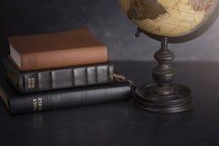 Bunt av biblar och ett jordklot på en mörk bakgrund arkivfoton