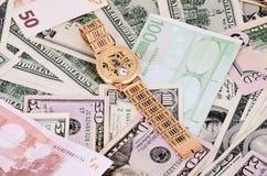 Bunt av 100 dollarräkningar och den guld- klockan på en full bakgrund Royaltyfri Bild